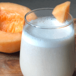 a subtle orange, creamy smoothie with vibrant melon in the background