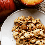 pumpkin in the background with roasted seeds in the forefront