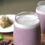 A purple smoothie in a short glass with spinach and blueberries as garnish next to a tea bag