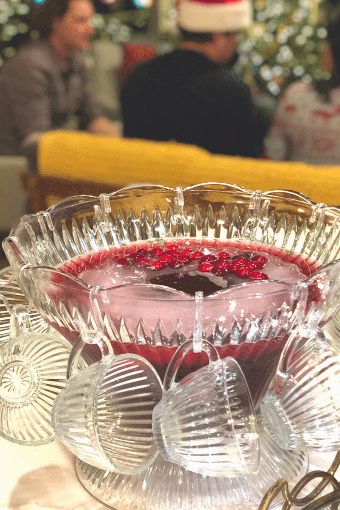 A big crystal bowl of crimson punch with glasses and a ladle with a holiday party in the background