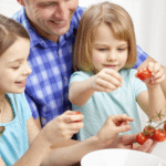 a family cooking together with kids hulling strawberries