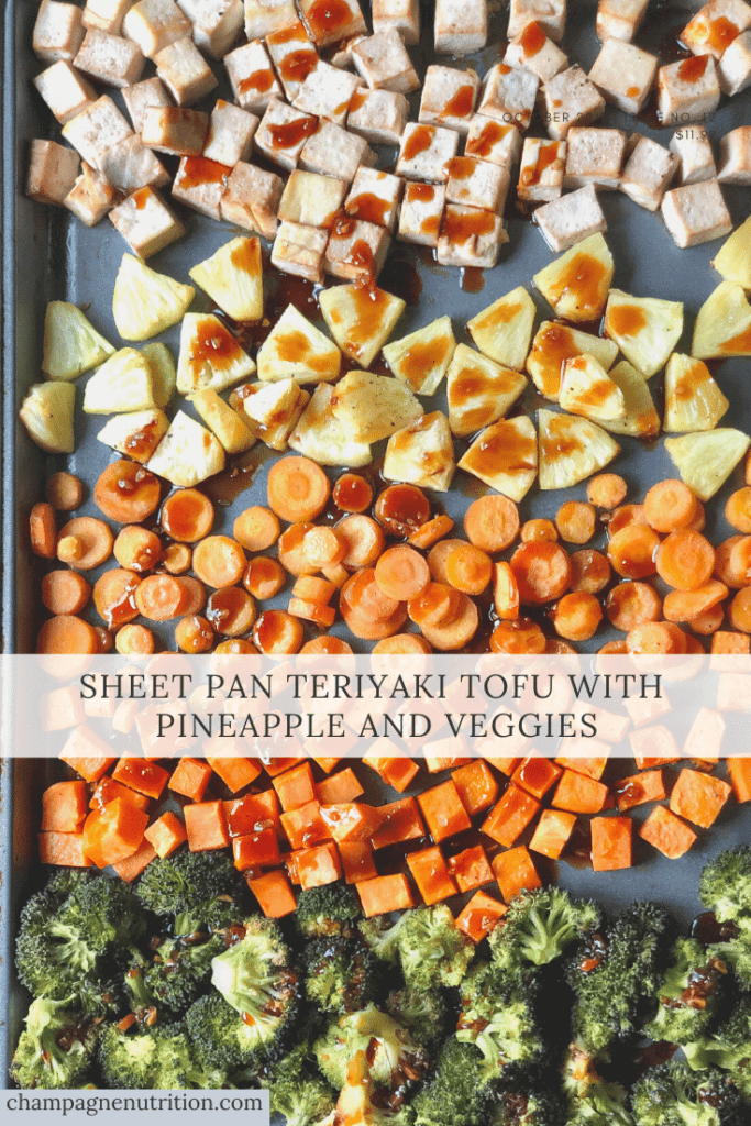 cooked, layered tofu and veggies on a sheet pan with sauce