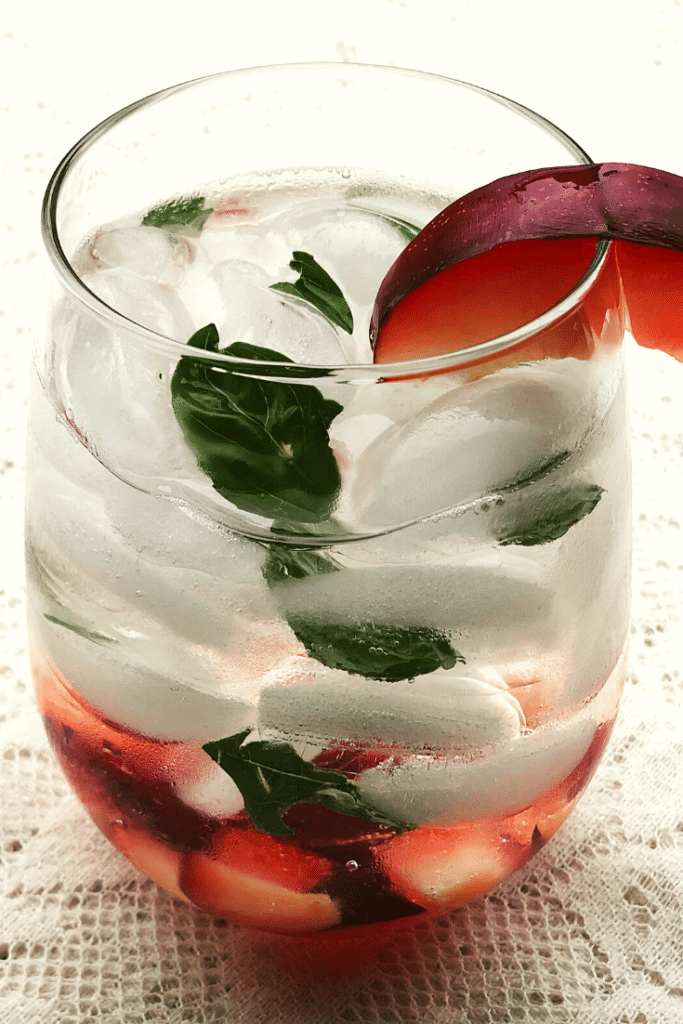 A glass full of ice, plums, basil and clear spirit cocktails