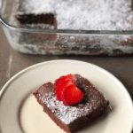 perfectly baked brownies with a strawberry and powdered sugar on top