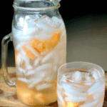 A large, glass pitcher and glass filled with ice and golden cantaloupe