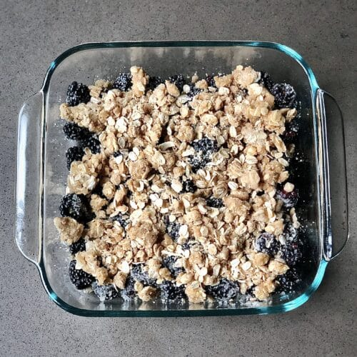 dark blackberries and a golden oat topping in a glass dish