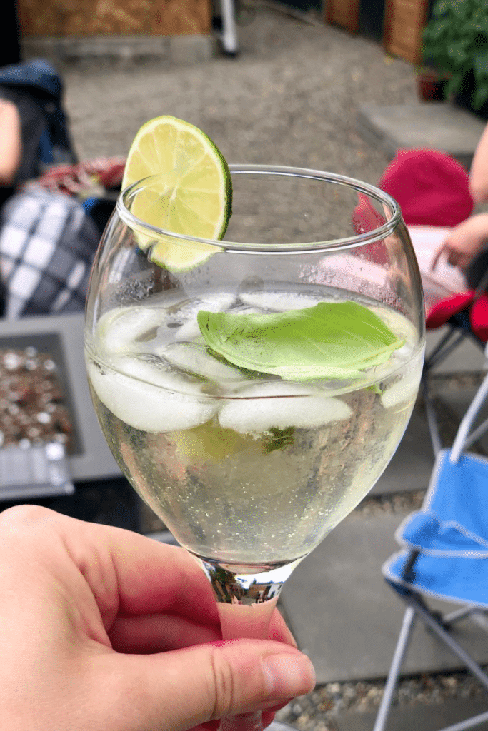 A clear, golden cocktail in a wine glass over ice with a lime and basil garnish