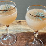 a lightly golden colored cocktail garnished with pine in a gold-rimmed glass